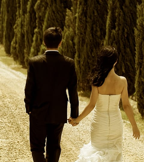 Bride and groom walking down a path.